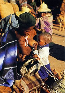 "A postcard from Lesotho.  The caption on this postcard reads""Mosotho woman weaving a basket"".  The breastfeedin part is seen as so normal, it's not even mentioned."